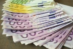 Kontanta eurosedlar fördelade ut på tabellen Arkivfoton
