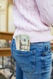 Kontanta pengar i jeansfack av den sexiga kvinnaänden Arkivfoto