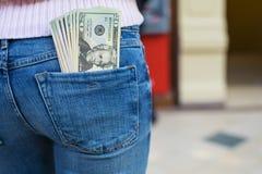 Kontanta pengar i jeansfack av den sexiga kvinnaänden Royaltyfri Bild