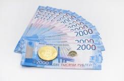 Kontanta rubel och elektronisk valutabitcoin På vitbakgrund arkivbilder