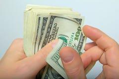 Kontanta US dollar i hand Arkivfoto