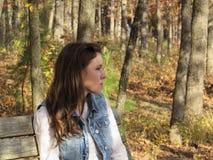 Kontemplacyjny młodej damy obsiadanie na ławce w jesień lesie Zdjęcie Royalty Free