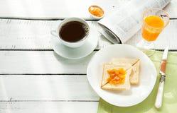 Kontinental frukost - kaffe, orange fruktsaft, rostat bröd Royaltyfria Bilder
