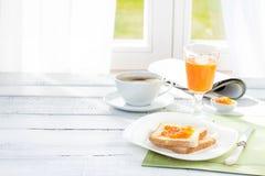 Kontinental frukost - kaffe, orange fruktsaft, rostat bröd Royaltyfri Foto