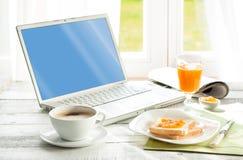 Kontinental frukost och bärbar datordator Arkivfoto