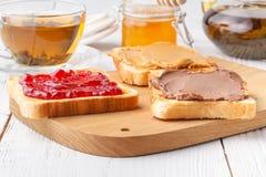 Kontinental frukost - rostat bröd, driftstopp, jordnötsmör, fruktsaft arkivfoton