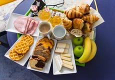 Kontinentales Frühstück gedient im Hotel mit der Früchte, heißer und kalter den Getränken der Hörnchen, des Käses, des Schinkens, stockbild