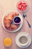 Kontinentales Frühstück - Kaffee, Hörnchen mit Stau, Erdbeeren Stockfotografie
