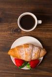 Kontinentales Frühstück mit Hörnchen, Kaffee und frischen Erdbeeren Lizenzfreie Stockfotos