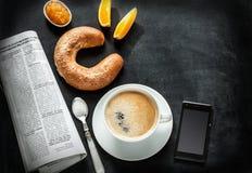 Kontinentales Frühstück und Handy auf schwarzer Tafel Lizenzfreies Stockbild