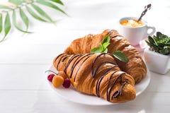 Kontinentales gebackenes Hörnchen des Frühstücks frisch verziert mit Stau und Schokolade auf Holztisch in einer Küche mit Kopie lizenzfreie stockfotografie