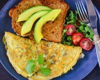 Kontinentalt frukost-omelett rostat bröd med avokadosallad fotografering för bildbyråer