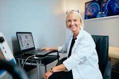Kontor för doktor Working In Hospital för stående kvinnligt med att le för dator royaltyfri foto
