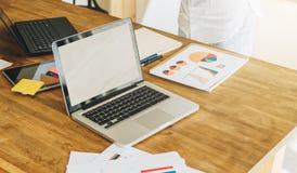 Kontor skrivbord Närbild av en bärbar dator på en trätabell Närliggande är pappers- diagram, diagram, diagram, en digital minnest Royaltyfria Bilder