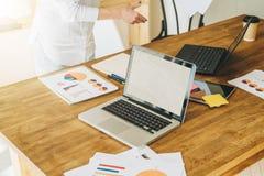 Kontor skrivbord Närbild av en bärbar dator på en trätabell Närliggande är pappers- diagram, diagram, diagram, en digital minnest Arkivfoton