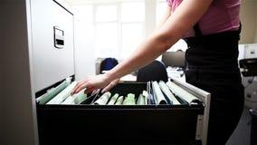 Kontoret: den kvinnliga kontorsarbetaren får mappen från dokumentskåpet