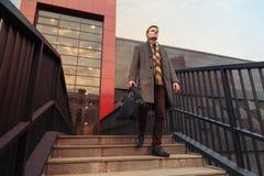 Kontoret klädde fashionably den unga affärsmannen med en portfölj som går till och med staden royaltyfria foton