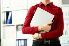 Kontorist i röd blus som kramar den gråa dokumentblockcloseupen arkivbild