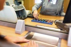 Kontorist som räknar kontanta pengar på bankkontoret royaltyfri foto
