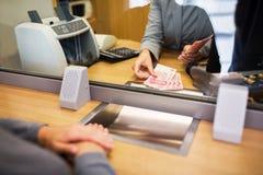 Kontorist som räknar kontanta pengar på bankkontoret fotografering för bildbyråer