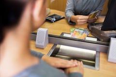 Kontorist som räknar kontanta pengar på bankkontoret arkivbild