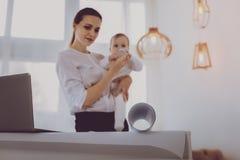 Kontorsadministratör som vårdar det lilla barnet, medan samarbeta med klienter royaltyfria bilder