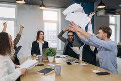 Kontorsarbetare firar aff?rsframg?ng och kastar upp legitimationshandlingar och dokument arkivbilder