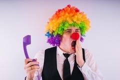 Kontorsarbetare i clownperuken, clownbegrepp på arbete Affärsman med clownperuken på vit arkivfoton
