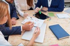 Kontorsarbetare i intervjun betraktar scheman På tabelldiagrammen, en minnestavla och anteckningsböcker Royaltyfri Bild