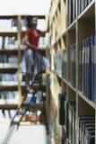 Kontorsarbetare på stege i mapplagringsrum Royaltyfri Bild