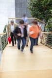 Kontorsarbetare som går upp trappa, rörelsesuddighet Arkivfoton