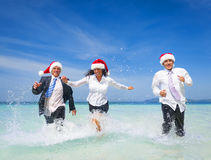 Kontorsarbetare som har gyckel på stranden på jul royaltyfri foto