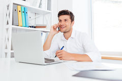 Kontorsarbetare som kallar på telefonen och använder bärbara datorn Royaltyfri Fotografi