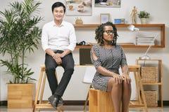 Kontorsarbetare som sitter på kontoret royaltyfri fotografi