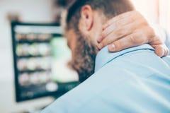 Kontorsarbetaren med halsen smärtar från sammanträde på skrivbordet hela dagen Arkivbilder