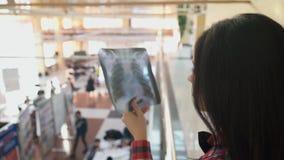 Kontorsarbetaren står i korridor och undersöker röntgenstrålefotografiet lager videofilmer