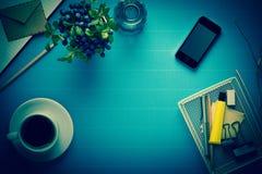 Kontorsarbetsplats, kontorsutrustning och kaffeavbrott på blå kräpp Royaltyfria Bilder