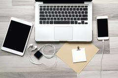 Kontorsarbetsplats med bärbara datorn, minnestavladatoren och smartphonen Fotografering för Bildbyråer