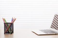 Kontorsarbetsplats med bärbara datorn och blyertspennor Royaltyfria Foton