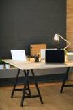 Kontorsarbetsplats med bärbara datorn och på den wood tabellen Royaltyfri Bild