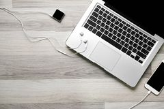 Kontorsarbetsplats med bärbara datorn och smartphonen på den wood tabellen Fotografering för Bildbyråer