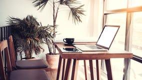 Kontorsarbetsplats med bärbara datorn på den wood tabellen mot fönstren Fotografering för Bildbyråer