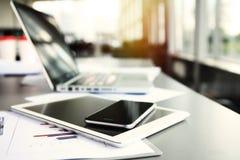 Kontorsarbetsplats med bärbara datorn på tabellen mot fönstren Fotografering för Bildbyråer