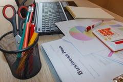 Kontorsarbetsplats med den penn-, anteckningsbok-, räknemaskin- och datorbärbara datorn på trätabellen Arkivfoto