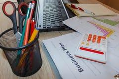 Kontorsarbetsplats med den penn-, anteckningsbok-, räknemaskin- och datorbärbara datorn på trätabellen Arkivbilder
