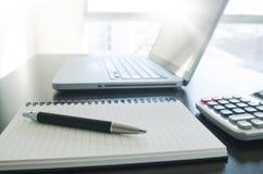 Kontorsarbetsplats med den penn-, anteckningsbok-, räknemaskin- och datorvarven royaltyfri fotografi