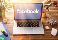 Kontorsarbetsplats med facebookskärmen Arkivbild