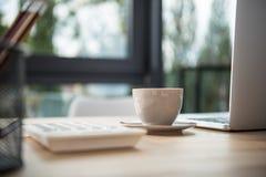Kontorsarbetsplats med kaffe- och bärbar datordatorer Arkivbilder