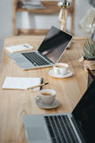 Kontorsarbetsplats med kaffe- och bärbar datordatorer Royaltyfria Bilder