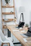 Kontorsarbetsplats med kaffe- och bärbar datordatorer Fotografering för Bildbyråer